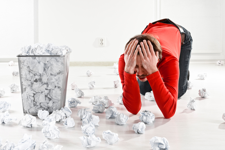 Frustrated, worried man with scattered paper balls on the floor